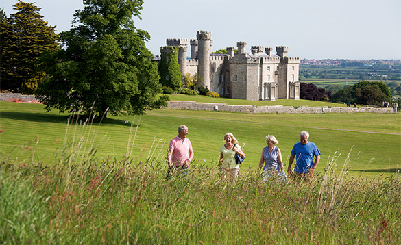 Group of adults walking through grassland with stone castle in background/