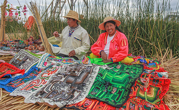Peruvian couple kneeling on reeds selling multi-coloured blankets/