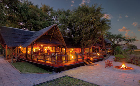 Nightime view of an African safari lodge with large veranda and paved area to the side and front with a lit firepit/