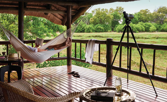 man laying in a hammock reading a book on the wooden veranda of a lodge set in the African country/