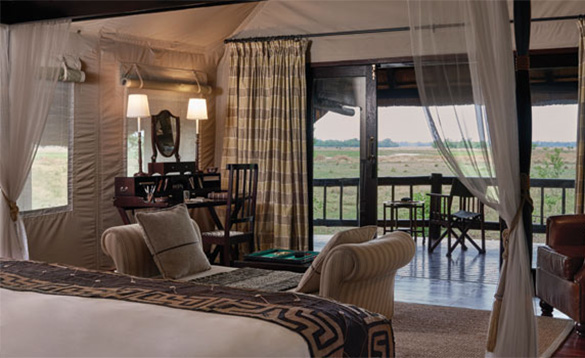 Bedroom at an african safari lodge with large open doors leading to a veranda with seating and views of the open countryside/