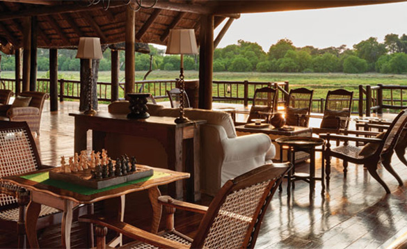 wooden tables with wicker chairs set on a large veranda of a safari lodge with views of the country/