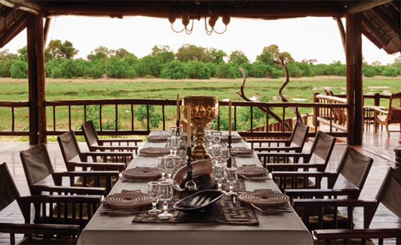 large table set for dinner with 5 seats down either side located on a veranda overlooking garssland leading to bushes/