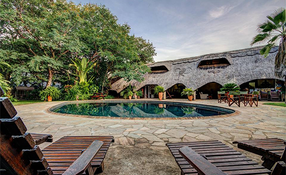 Sun loungers around a circular pool at Bayete Guest Lodge in Botswana/