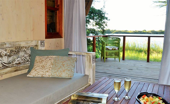 Decked seating area with view of a lake at Chobe Bakwena Lodge/