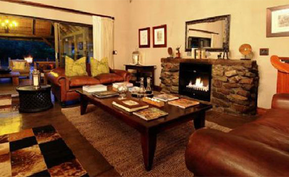 lounge in a safari lodge with fire buring in a feature stone fireplace and brown leather sofas arranged either side of large coffee table/