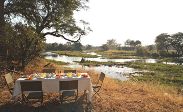 Table and six chairs set for dinner located in the African bush/