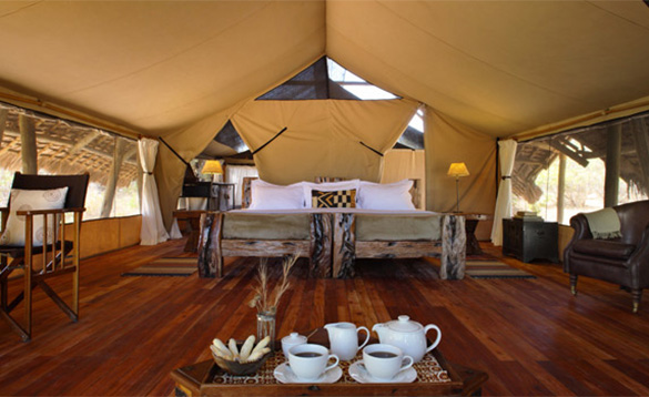 large bedroom in an African safari lodge with open side and large double bed, leather chairs and tea tray/