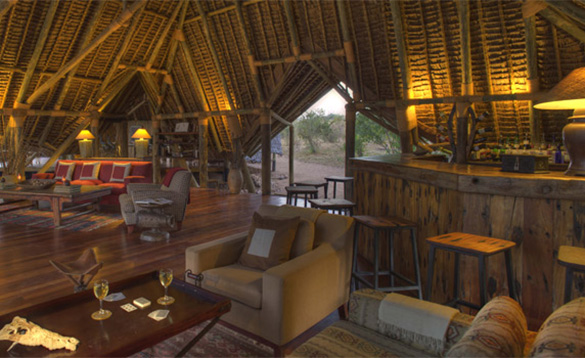 lounge of an African safari lodge with bar area and sofas arranged around tables/
