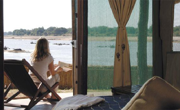 lady sitting on a deck chair on the veranda of a safari lodge overlooking a river towards bushes in the distance/