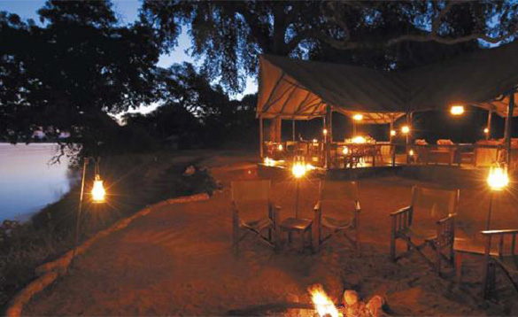 nighttime picture of candlelit vernada and chairs around a lit firepit/