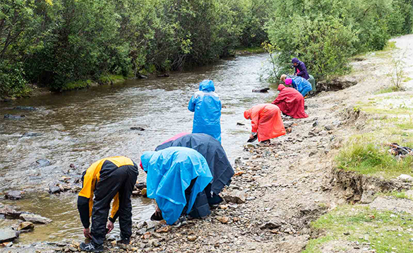 Group of people panning for gold beside a river in the Yukon/