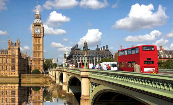 London bus travelling across the Thames heading towards Big Ben and the Houses of Parliament/