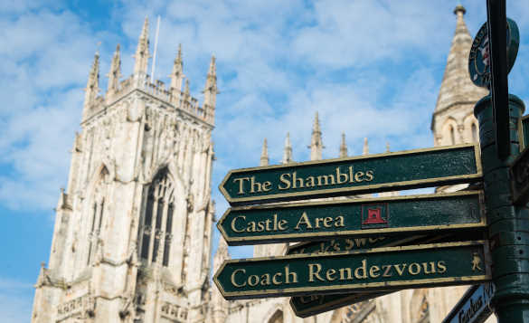 York Minster with a sign post showing the way to the Shambles and Castle area/