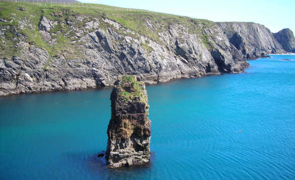 Calm blue seas lapping against craggy cliffs in Co Donegal Ireland/