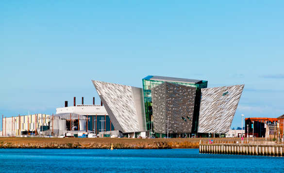 View across water to the Titanic Belfast, an aluminium coated angular building/