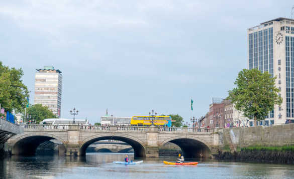 Two people in canoes paddling up to a stone bridge that spans the River Liffey in Dublin/
