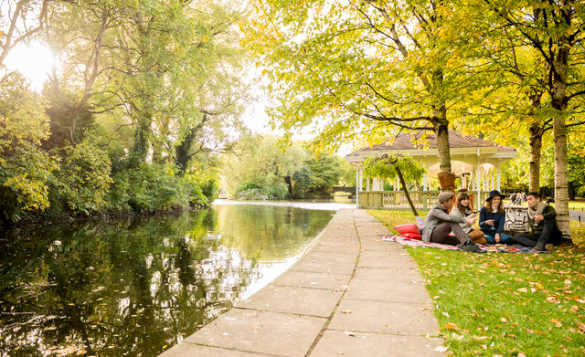 Group of four people sitting on a blanket in the shade of trees enjoying a picnic beside a canal/