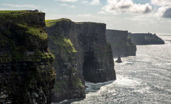 Waves breaking against the Cliffs Of Moher in Ireland on a sunny day/