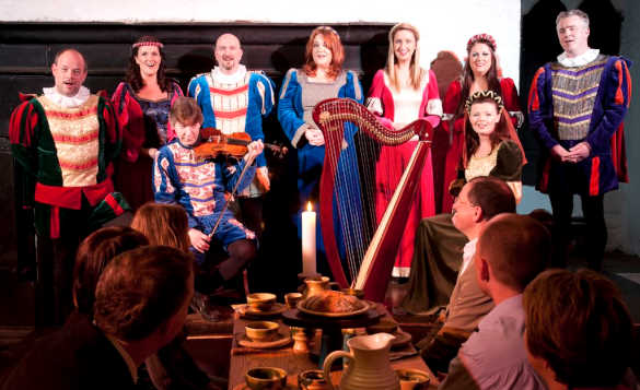 People enjoying a banquet at Bunratty Castle, Co Clare while being entertained with musicians and singers in medieval costumes/