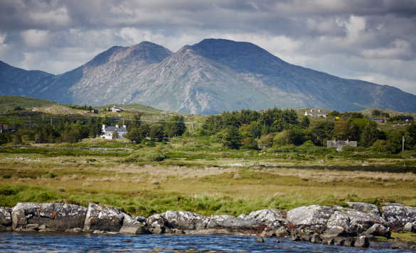 White cottage set at the foot of mountains amongst the green countryside of Connemara Ireland/