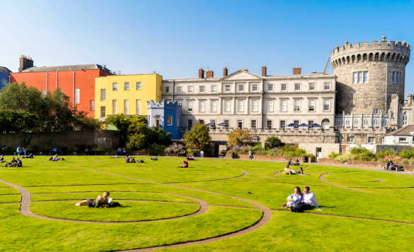 People relaxing and enjoying the sunshine beside Dublin Castle/