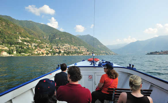 Group of people taking a boat ride across Lake Como and admiring the stunning scenery/