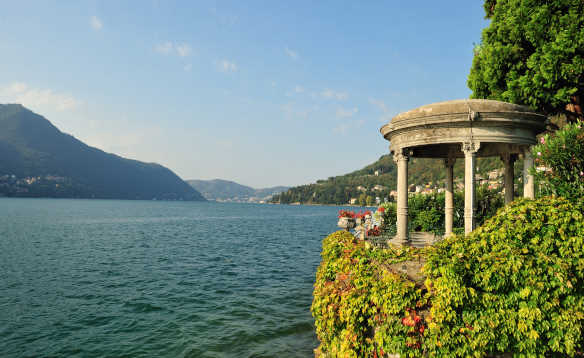 View across Lake Como to tree covered hillsides leading down to the lake shore/