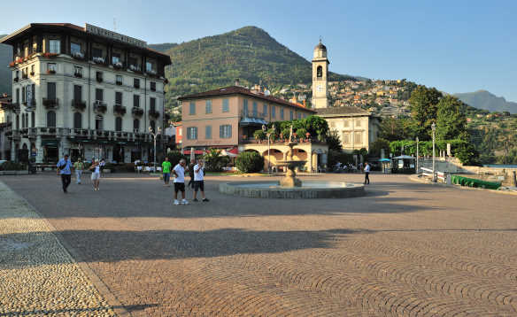 People walking beside a fountain in the middle of Cernobbio Square, Lake Como/
