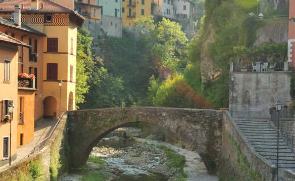 Brightly painted houses on a cliff side with a stone Roman Bridge crossing a stream/