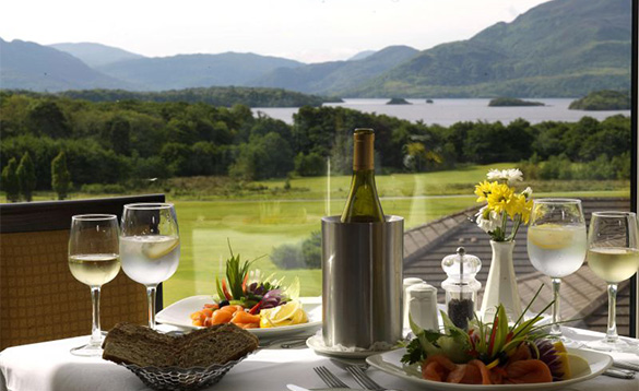 Dining table with smoked salmon and wine set for two people and magnificent views over lakes towards mountains at the Castlerosse Hotel in Killarney  /