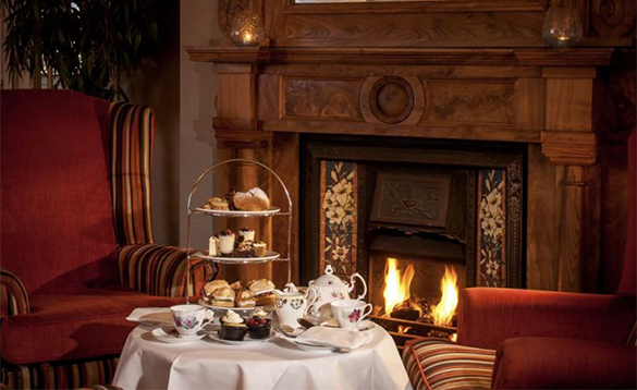 Table set with an afternoon tea beside a roaring log fire /