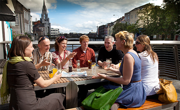 Group of people enjoying drinks and chatting in the sunshine beside the river in Cork city/
