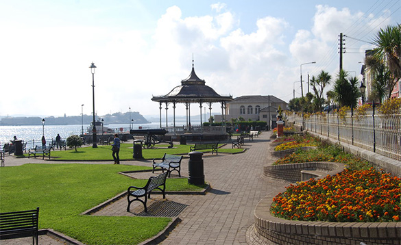 The promenade in Cobh in Ireland with bandstand, lawns and colourful flower beds/