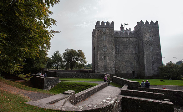 People walking around the grounds infront of Bunratty Castle/