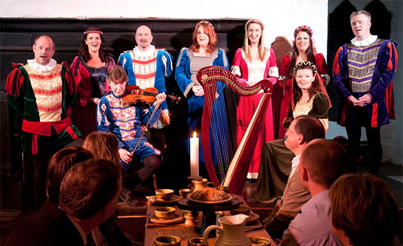 People enjoying a medieval banquet at Bunratty Castle and being entertained by singers and musicians in Medieval dress/