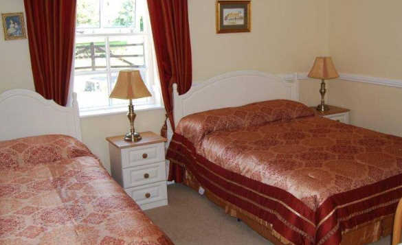 Bedroom at Crannmor House, Trim with double and single bed either side of a bedside cabinet/