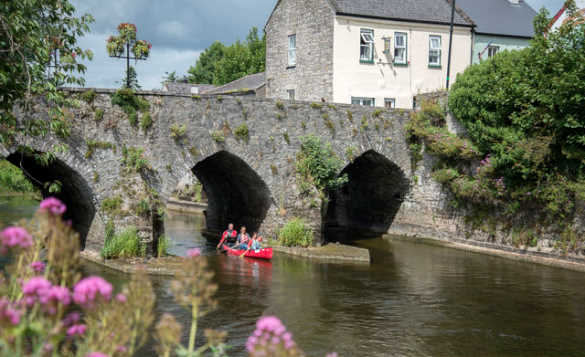 Group of people canoeing underneath an arched stone bridge in Trim, Co Meath/