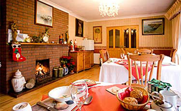 Dining room at Evergreen B&B with fire burning in brick built fireplace and tables set for breakfast/