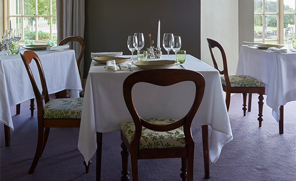 Dining room with tables set for dinner at the Gregan's Castle Hotel/
