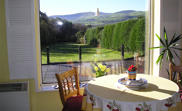 Table and chairs at Innisfree self-catering cottage next to a window with views over the Wicklow mountains/