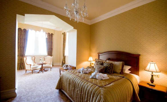Luxurious bedroom in Kilronan Castle with double bed and archway leading to separate seating area/