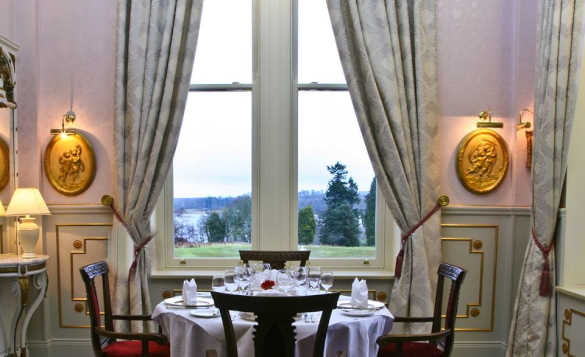 Dining table and four chairs set for lunch beside a window with views over trees and lake at Kilronan Castle/