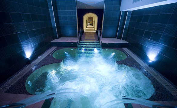 Spa pool at Kilronan Castle with dark blue wall tiles and underwater lighting/