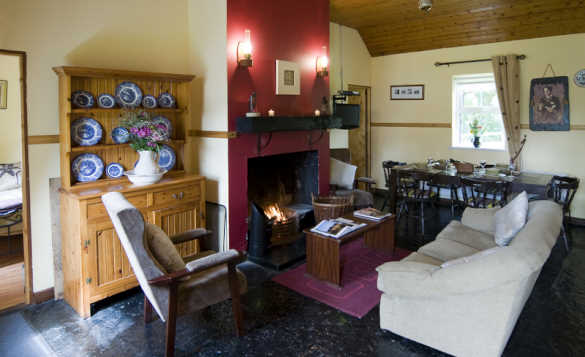 Open fire burning in the lounge/dining room at McGuires Cottages, Drumshanbo/