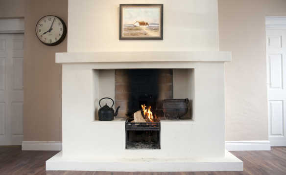 Open fireplace with fire burning in McGuires Cottages, Drumshanbo/