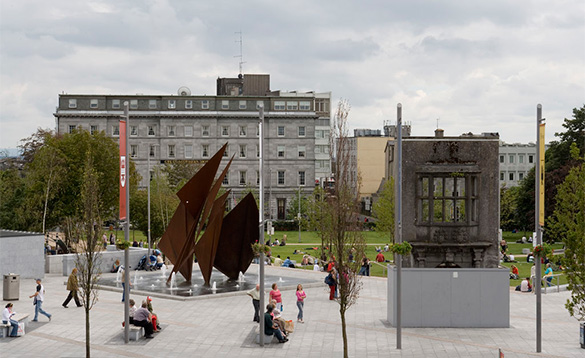 People walking past a statue and fountain in Eyre Square, Galway/