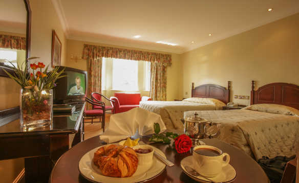 Croissant and coffee set on a table in a hotel bedroom at the Twin Trees Hotel/