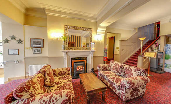 Lounge at the Twin Trees Hotel with two sofas either side of a coffee table infront of a log burning stove./