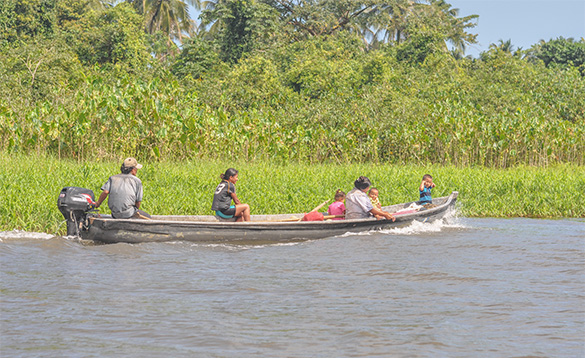 Nicaraguan family travelling along a river in a boat with outboard motor/